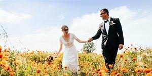 ein Brautpaar läuft lachend durch ein Mohnfeld